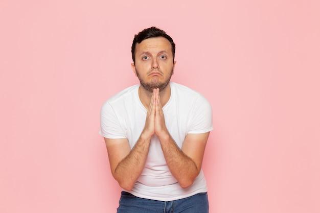 Een vooraanzicht jonge man in wit t-shirt en spijkerbroek poseren en bedelen op het roze bureau man kleur emotie pose