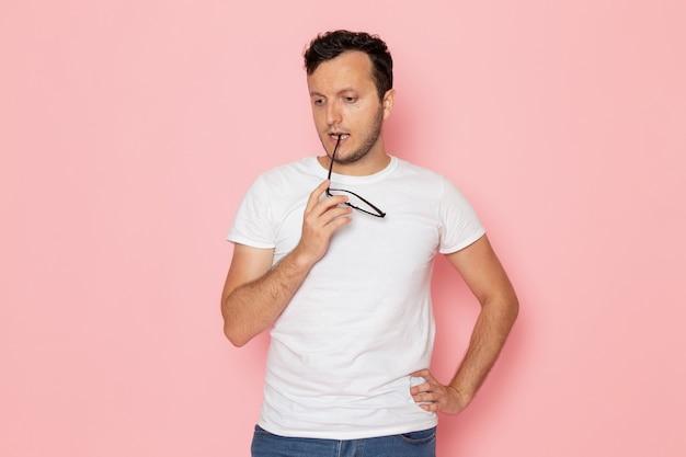 Een vooraanzicht jonge man in wit t-shirt en spijkerbroek poseren en denken op het roze bureau man kleur emotie pose