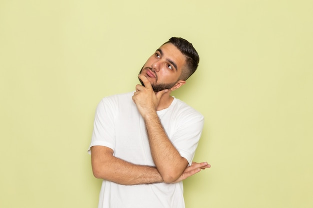 Een vooraanzicht jonge man in wit t-shirt met denkende uitdrukking