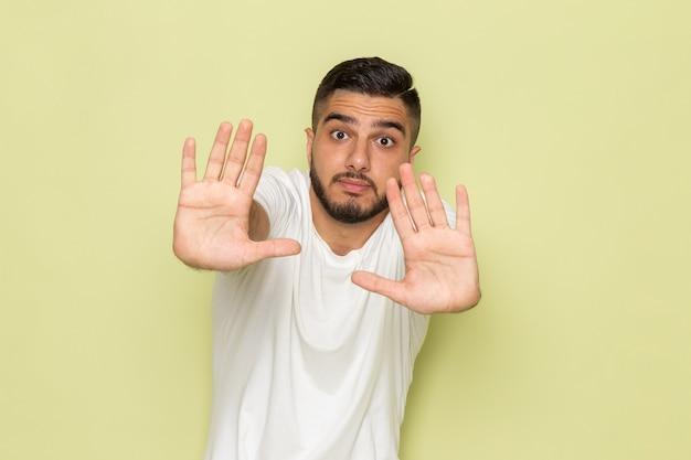Een vooraanzicht jonge man in wit t-shirt met een bange uitdrukking