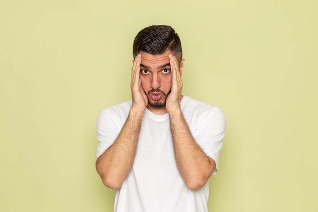 Een vooraanzicht jonge man in wit t-shirt met een verwarde uitdrukking