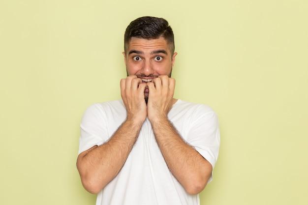 Een vooraanzicht jonge man in wit t-shirt met nerveuze uitdrukking