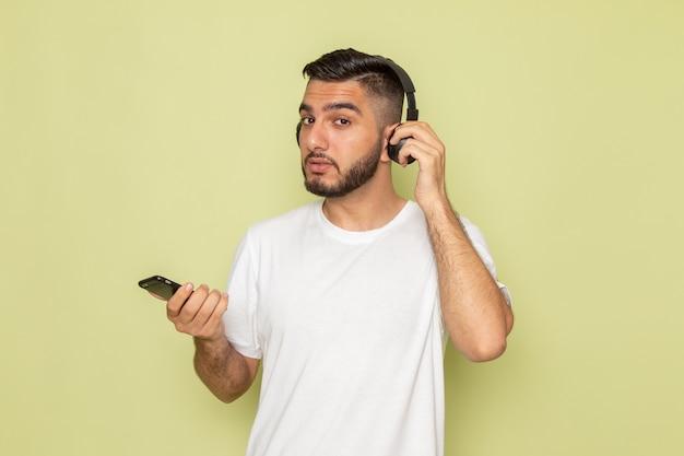 Een vooraanzicht jonge man in wit t-shirt met telefoon en luisteren naar muziek