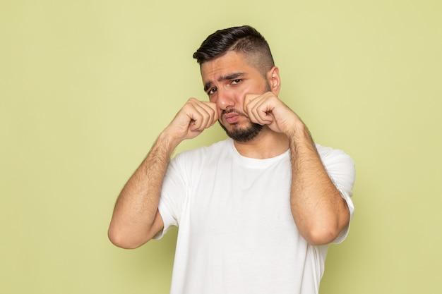 Een vooraanzicht jonge man in wit t-shirt nep huilen