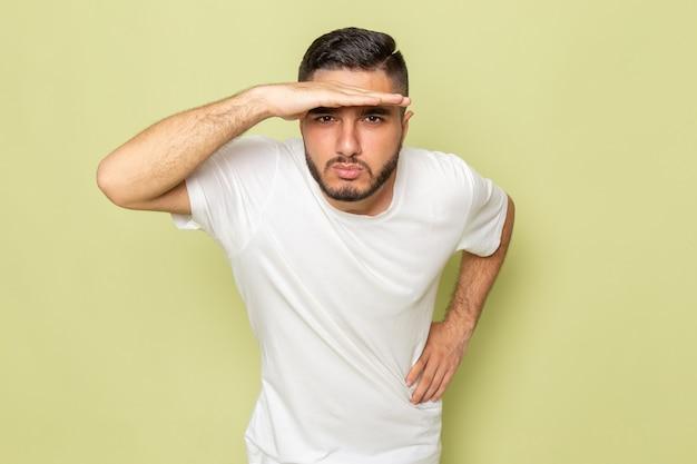 Een vooraanzicht jonge man in wit t-shirt op zoek in de verte