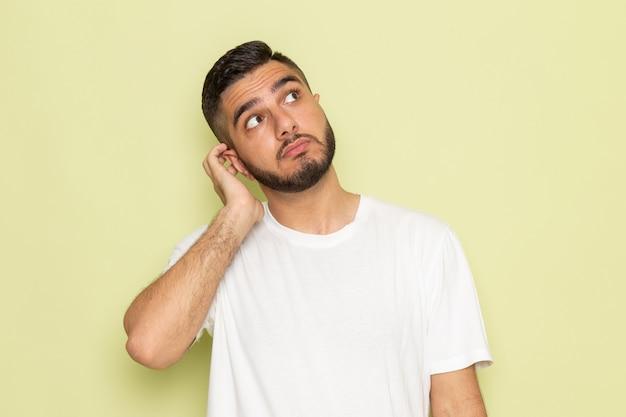 Een vooraanzicht jonge man in wit t-shirt poseren met denken expressie