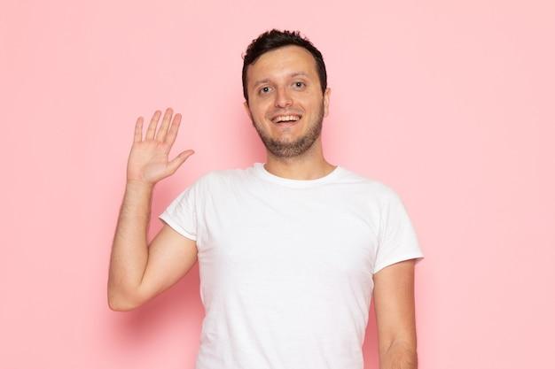 Een vooraanzicht jonge man in wit t-shirt poseren met een glimlach