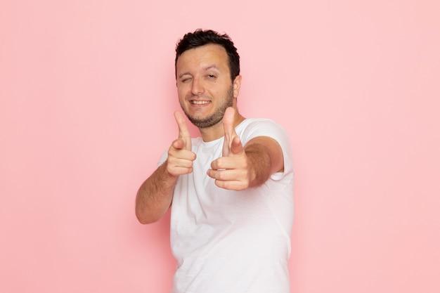 Een vooraanzicht jonge man in wit t-shirt poseren met grappige uitdrukking