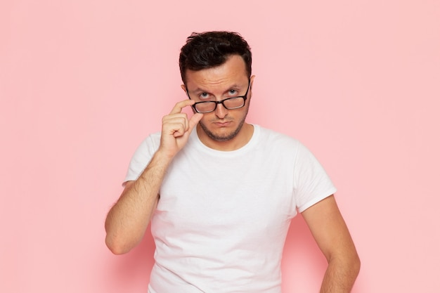 Een vooraanzicht jonge man in wit t-shirt poseren met optische zonnebril