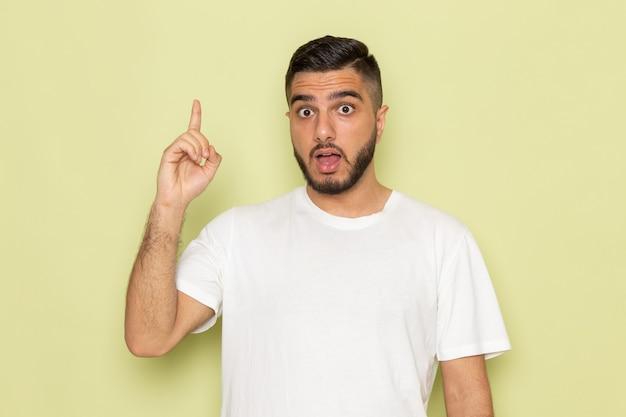 Een vooraanzicht jonge man in wit t-shirt poseren model