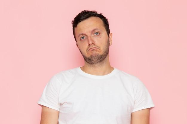 Een vooraanzicht jonge man in wit t-shirt staat met verwarde uitdrukking