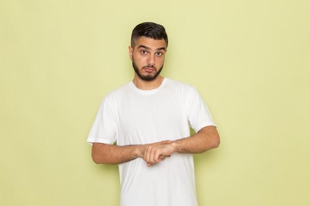 Een vooraanzicht jonge man in wit t-shirt wijzend op zijn pols