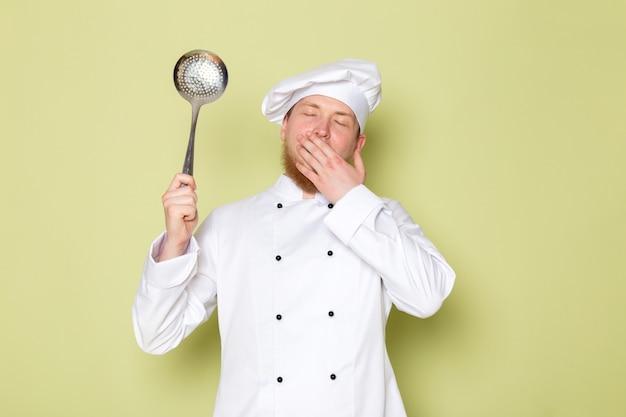 Een vooraanzicht jonge mannelijke kok in wit kokkostuum witte hoofd glb die het grote zilveren lepel niezen houden