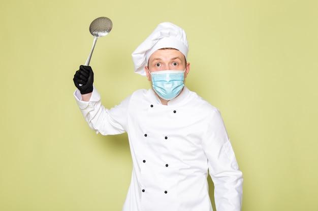 Een vooraanzicht jonge mannelijke kok in witte kok pak witte hoofd dop in zwarte handschoenen blauw beschermend masker met grote metalen lepel bedreigend