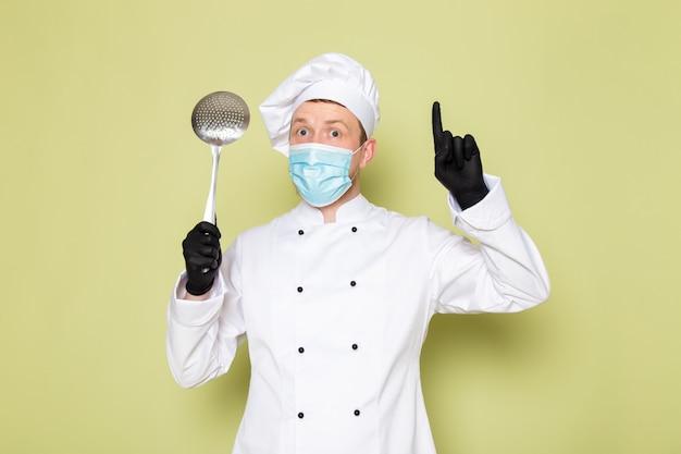 Een vooraanzicht jonge mannelijke kok in witte kok pak witte hoofd dop in zwarte handschoenen blauw beschermend masker met grote metalen lepel