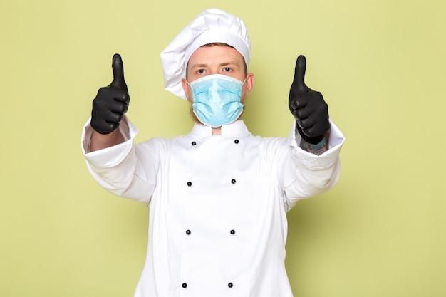 Een vooraanzicht jonge mannelijke kok in witte kok pak witte kop cap in zwarte handschoenen blauw beschermend masker met geweldige teken