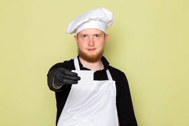 Een vooraanzicht jonge mannelijke kok in zwart shirt met witte cape wit hoofd cap in zwarte handschoenen met grijze kaart lachend