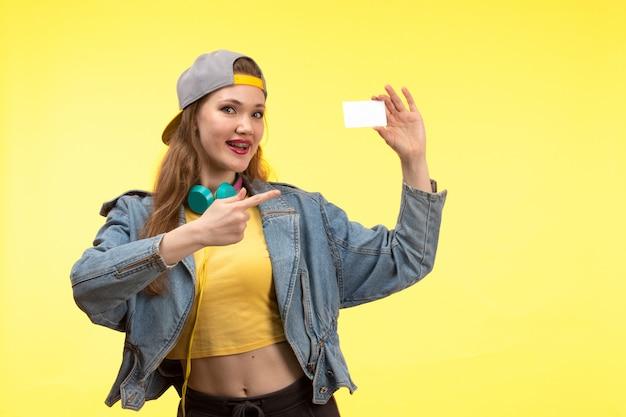 Een vooraanzicht jonge moderne vrouw in gele overhemd zwarte broek en jean jas met gekleurde koptelefoon lachend