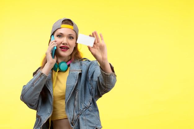 Een vooraanzicht jonge moderne vrouw in gele overhemd zwarte broek en jean jas met gekleurde oortelefoons met witte kaart praten over de telefoon poseren