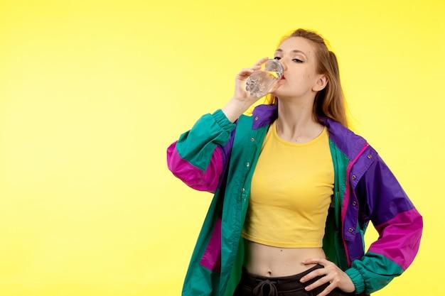 Een vooraanzicht jonge moderne vrouw in gele overhemd zwarte broek en kleurrijk jas drinkwater