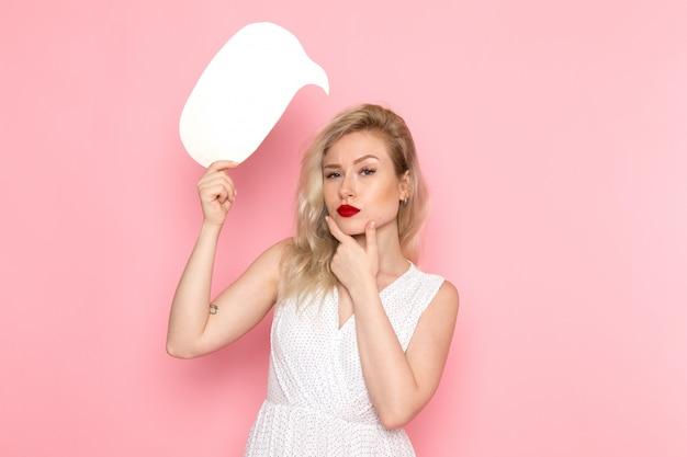 Een vooraanzicht jonge mooie dame die in witte kleding wit teken houdt