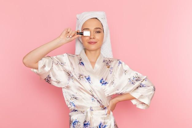 Een vooraanzicht jonge mooie dame in het nagellak van de badjasholding