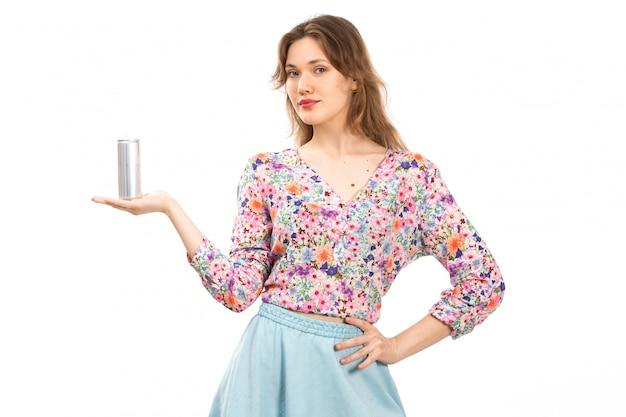 Een vooraanzicht jonge mooie dame in kleurrijke bloem ontworpen shirt en blauwe rok met zilveren blikje drinken op de witte