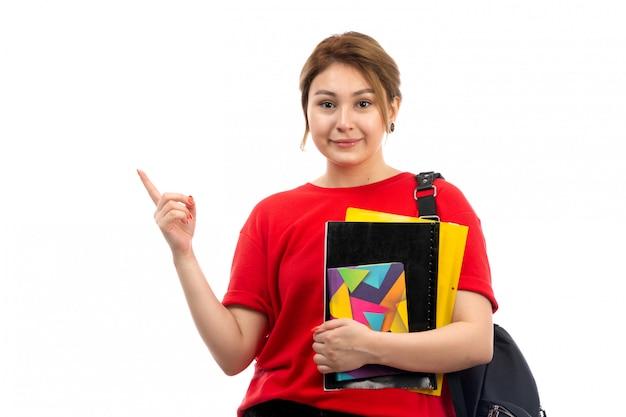 Een vooraanzicht jonge mooie dame in rode t-shirt zwarte jeans die verschillende voorbeeldenboeken en dossiers houdt die met zak op het wit glimlachen