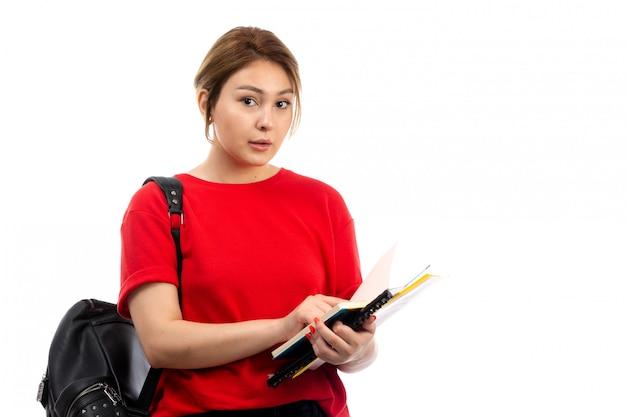 Een vooraanzicht jonge mooie dame in rode t-shirt zwarte jeans die verschillende voorbeeldenboeken en dossiers met zak op het wit houdt