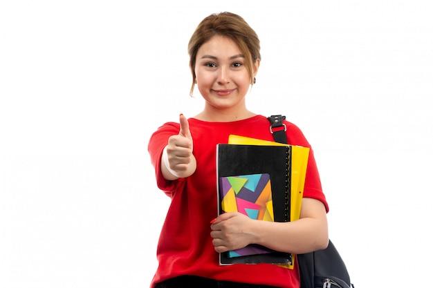 Een vooraanzicht jonge mooie dame in rode t-shirt zwarte spijkerbroek met verschillende schriften en bestanden glimlachend als teken met tas op de witte