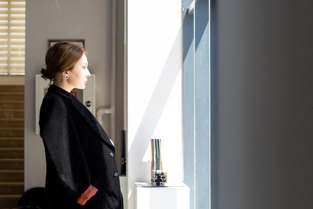 Een vooraanzicht jonge mooie dame in wit overhemd donkere jas zwarte broek kijken naar de afstand in de hal te wachten tijdens de bouw dag bouwactiviteit