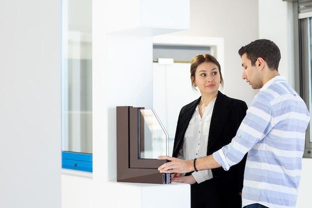 Een vooraanzicht jonge mooie dame in wit overhemd donkere jas zwarte broek samen met jonge man bespreken iets tijdens de dag opbouwen van baan activiteit