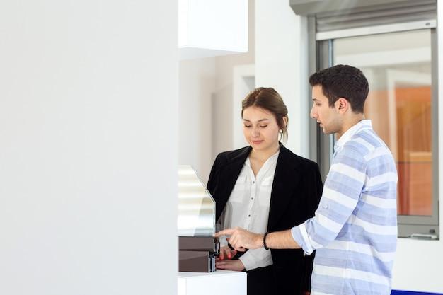 Een vooraanzicht jonge mooie dame in wit overhemd donkere jas zwarte broek, samen met jonge man bespreken van werk tijdens de dag bouwen van baanactiviteit