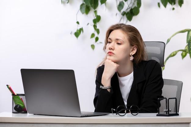 Een vooraanzicht jonge mooie dame in wit overhemd en zwarte jas met behulp van haar laptop voor tafel met bladeren hangen