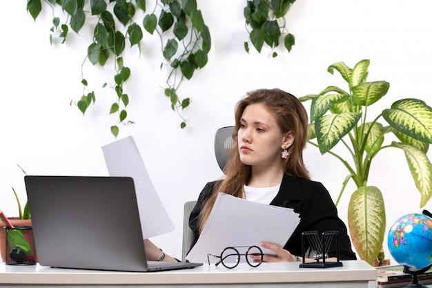Een vooraanzicht jonge mooie dame in wit overhemd en zwarte jas werken met documenten met behulp van haar laptop voor tafel met bladeren hangen