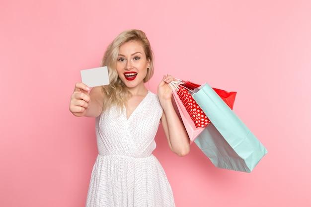Een vooraanzicht jonge mooie dame in witte jurk bedrijf shopping pakketten met een glimlach op haar gezicht