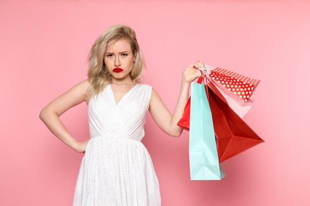 Een vooraanzicht jonge mooie dame in witte jurk bedrijf shopping pakketten met ontevreden uitdrukking