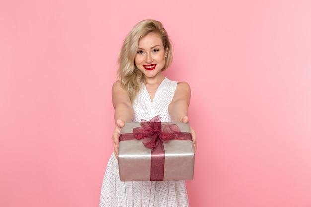 Een vooraanzicht jonge mooie dame in witte jurk met huidige doos met een glimlach op haar gezicht