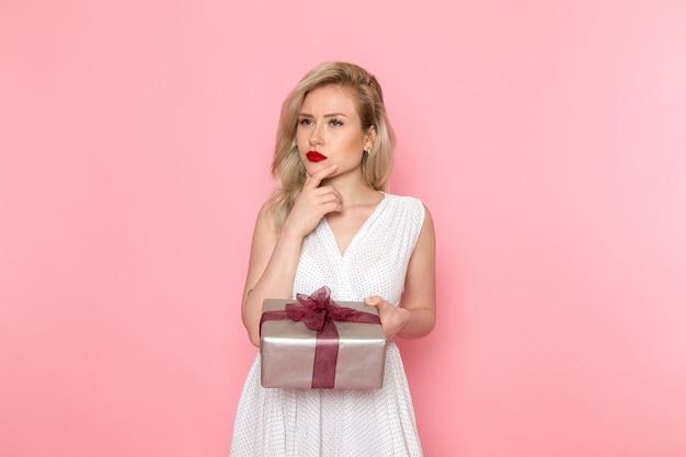 Een vooraanzicht jonge mooie dame in witte jurk met huidige doos
