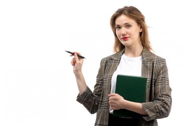 Een vooraanzicht jonge mooie dame in witte t-shirt zwarte jeans en jas met groene boek en pen glimlachend op het wit