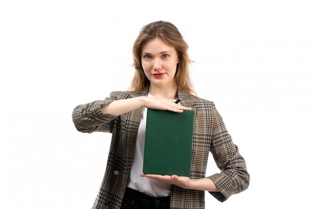 Een vooraanzicht jonge mooie dame in witte t-shirt zwarte jeans en jas met groene boek glimlachend op het wit