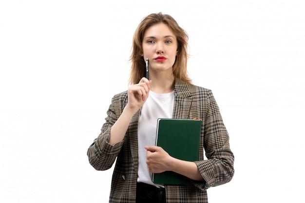 Een vooraanzicht jonge mooie dame in witte t-shirt zwarte jeans en jas met groene boek op de witte