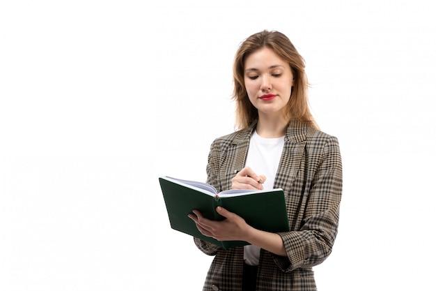 Een vooraanzicht jonge mooie dame in witte t-shirt zwarte jeans en jas met groene boek opschrijven op de witte