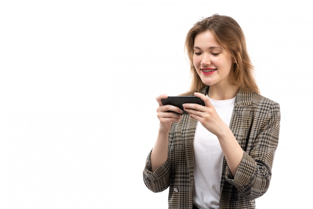Een vooraanzicht jonge mooie dame in witte t-shirt zwarte jeans en jas met smartphone glimlachend op de witte