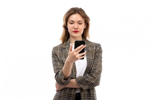 Een vooraanzicht jonge mooie dame in witte t-shirt zwarte jeans en jas met smartphone op de witte