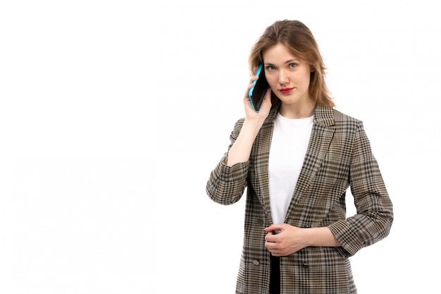 Een vooraanzicht jonge mooie dame in witte t-shirt zwarte jeans en jas met smartphone praten op de witte