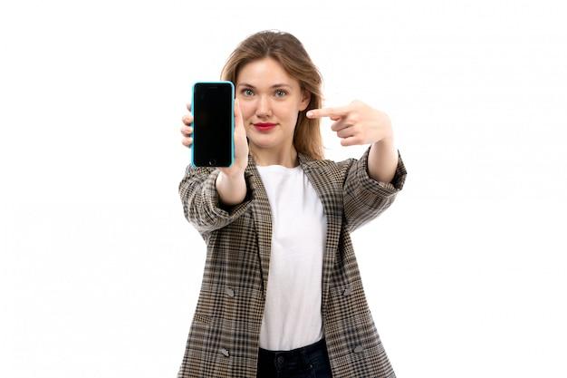 Een vooraanzicht jonge mooie dame in witte t-shirt zwarte jeans en smartphone van de laagholding die op het wit glimlachen