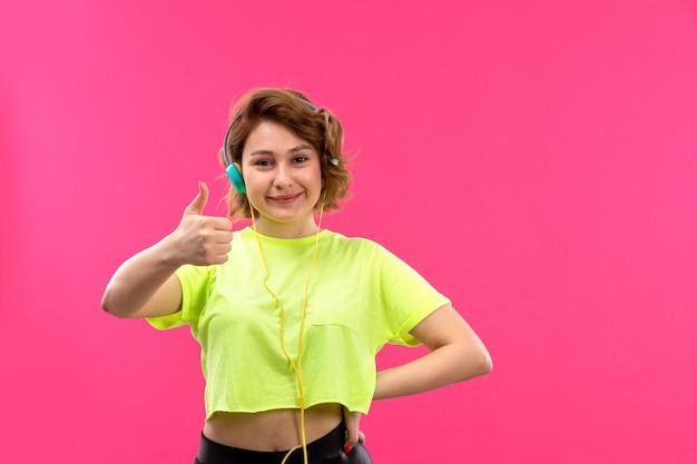 Een vooraanzicht jonge mooie dame in zuur gekleurde shirt zwarte broek met blauwe koptelefoon luisteren naar muziek gelukkig lachend