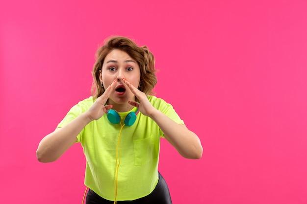 Een vooraanzicht jonge mooie dame in zuurkleurige overhemd zwarte broek met blauwe koptelefoon bellen
