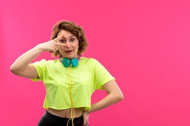 Een vooraanzicht jonge mooie dame in zuurkleurige overhemd zwarte broek met blauwe oortelefoons gelukkig